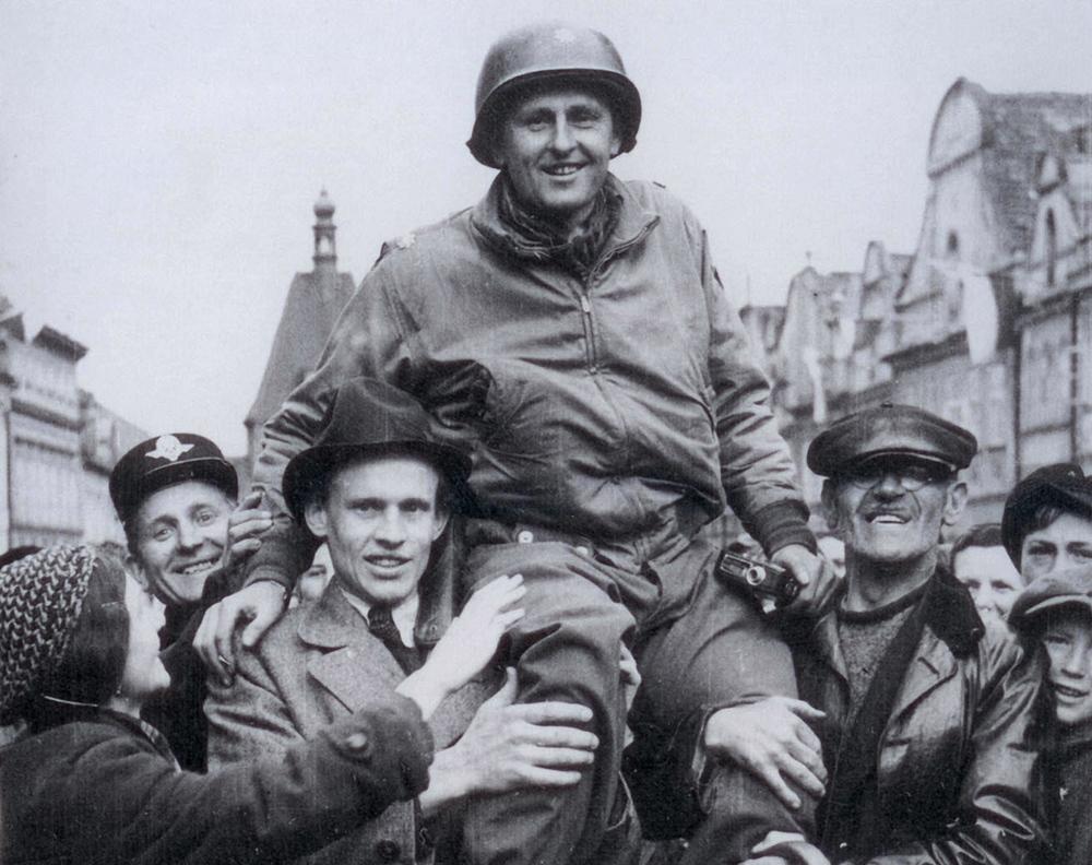 Matt Konop na ramenou obyvatel Domažlic 4. května 1945. Americká armáda právě osvobozuje české pohraničí. Foto: archív Patricka Dewana